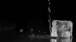 Water in super slow motion falling on ice cubes Footage