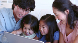 Family laughing while using a tablet computer Footage