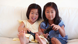 Two sisters playing a games console together Live Action