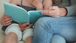 Mother helping her daughter read a book Footage