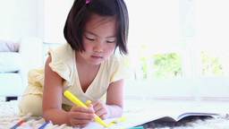 Girl using a marker to colour in a colouring book Live Action