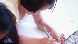 Girl colouring while lying next to her sister Footage