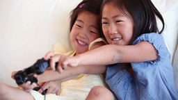 Two sisters playing a games console against each other Live Action
