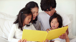 Parents reading a book to their children Footage