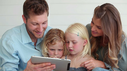 Family using a tablet computer as they sit togethe Footage