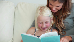 Girl laughing as she reads a book with her mother Footage