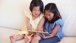 Two girls happily looking at a tablet computer Footage
