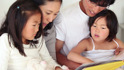 Parents reading a book to their children as they s Footage