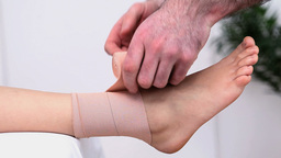 Physiotherapist strapping the ankle of a woman Footage