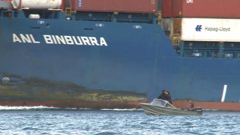 small boat passed by big container ship Stock Video Footage