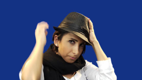 Young woman putting on hat, blue screen background Stock Video Footage