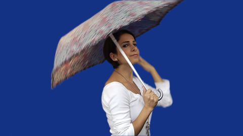 Young woman opening umbrella blue screen background Stock Video Footage
