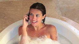Woman taking a bath while calling Footage