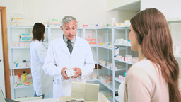 Smiling pharmacist talking to a colleague in front Footage