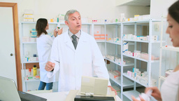 Pharmacist holding a prescription with a customer Footage