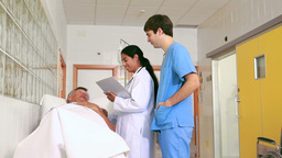 Doctor and nurse talking with a patient lying on a Footage