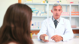 Pharmacist talking to a customer while holding a b Footage