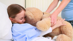 Happy woman giving a teddy bear to a girl in a bed Live Action