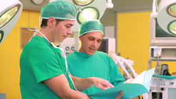 Two surgeons smiling while holding files in a surg Footage