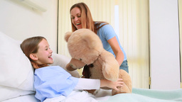 Happy woman giving a teddy bear to a girl in a bed Footage