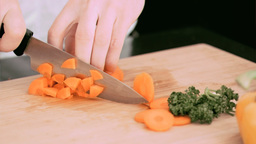 Woman cutting a carrot into cubes in slow motion Footage