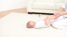 Woman playing with a baby on the carpet Footage