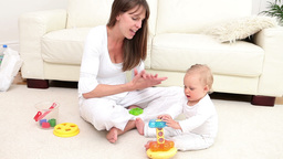 Woman and a baby playing with a toy Footage