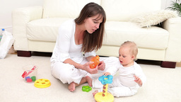 Woman and baby playing with a toy Footage