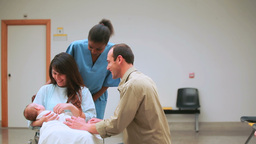 Nurse with a mother and a father with their baby o Footage