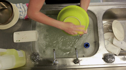 Cleaner washing the dishes at a sink Footage