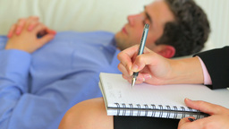 Man lying on a sofa while with therapist making notes ライブ動画