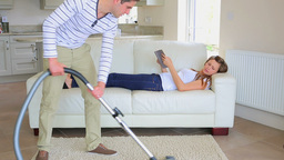 Woman relaxes on couch while man is hoovering Footage