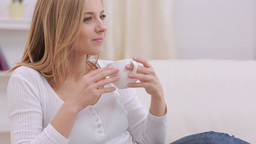 Calm woman thinking while drinking a hot drink Live Action