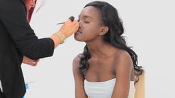 Woman sitting while getting eye makeup done Footage
