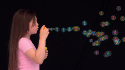 Side view of a little girl making bubbles Footage