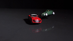 Red toy car crashing into green toy car Footage
