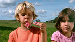 Small boy blowing bubbles with a girl Footage