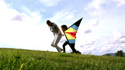 Woman and her daughter running with kite Footage