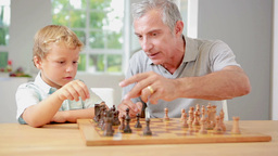Child learning to play chess with his grandpa Footage