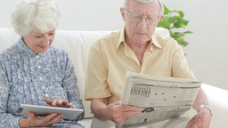 Old couple using a tablet and a newspaper Footage