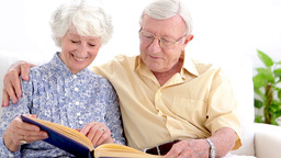 Old couple looking at photo album Footage