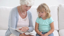 Grandmother and granddaughter reading a book Footage