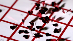 Dark red heart confetti dropping on calendar Footage