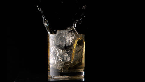 Ice cubes falling into whiskey Footage