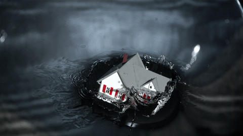 Miniature model house falling into grey water Footage