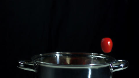 Cherry tomatoes falling into saucepan Footage