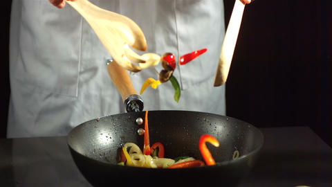 Chef mixing vegetable stir fry in a wok Footage