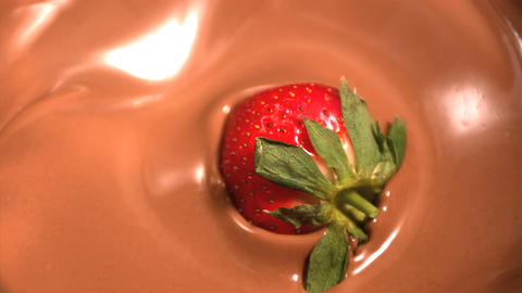 Strawberry dropping into melted chocolate close up Footage