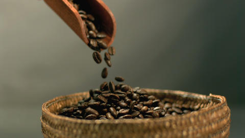 Coffee beans pouring from wooden scooper to basket Footage