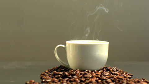 Steam rising from cup of coffee on pile of coffee beans Footage